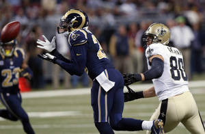 Photo - St. Louis Rams safety T.J. McDonald, left, intercepts a pass intended for New Orleans Saints tight end Jimmy Graham during the first quarter of an NFL football game, Sunday, Dec. 15, 2013, in St. Louis. (AP Photo/Charles Rex Arbogast)