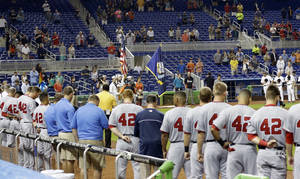 Photo - Baseball players and fans stand during a moment of silence for the victims of explosions at the Boston Marathon, before the start of a baseball game between the Miami Marlins and the Washington Nationals, Monday, April 15, 2013 in Miami. The players were wearing Jackie Robinson's No. 42. (AP Photo/Wilfredo Lee)