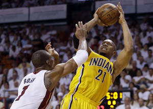 Photo - Indiana Pacers forward David West (21) attempts a basket over Miami Heat defender Chris Bosh (1) during the first half of Game 2 in their NBA basketball Eastern Conference finals playoff series, Friday, May 24, 2013, in Miami. (AP Photo/Lynne Sladky)