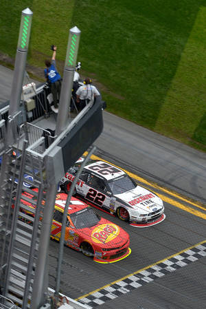 Photo - Regan Smith (7) beats Brad Keselowski (22) at the finish line to win the NASCAR Nationwide Series auto race at Daytona International Speedway in Daytona Beach, Fla., Saturday, Feb. 22, 2014. (AP Photo/Phelan M. Ebenhack)