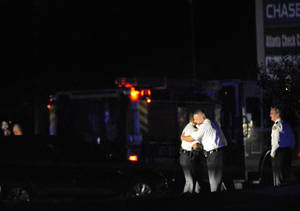 photo -   Law enforcement personnel embrace early Sunday, Nov. 4, 2012, as others investigate the scene of an Atlanta Police Department helicopter crash that killed two officers aboard the aircraft when it crashed near a shopping center late Saturday, Nov. 3, 2012. (AP Photo/David Tulis)
