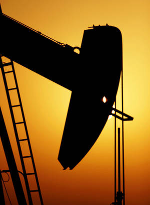 Photo - An oil pump works in the Sakhir, Bahrain, desert oil fields at sunset Tuesday, July 3, 2012. The price of oil jumped more than 4 percent Tuesday to the highest level since May on renewed fears of a military conflict with Iran. (AP Photo/Hasan Jamali)