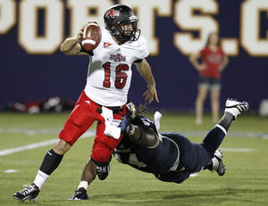 Photo -   Florida International's Darrian Dyson, right, pursues Arkansas State quarterback Ryan Alpin in the first quarter of an NCAA college football game at FIU Stadium in Miami, Thursday, Oct. 4, 2012. (AP Photo/The Miami Herald, Charles Trainor Jr.) MAGAZINES OUT