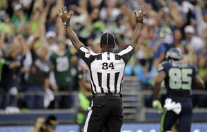 Photo - Official Derrick Rhone-Dunn (84) calls a Seattle touchdown during the first half of an NFL football game Green Bay Packers and Seattle Seahawks , Monday, Sept. 24, 2012, in Seattle. (AP Photo/Ted S. Warren)