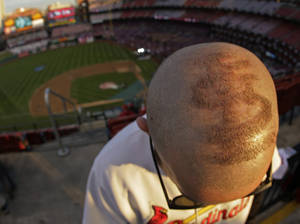 Photo - St. Louis Cardinals fan Jake McGrail shaved a design on the top of his head before Game 5 of baseball's World Series against the Boston Red Sox Monday, Oct. 28, 2013, in St. Louis. (AP Photo/Charlie Riedel)