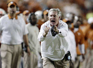 Photo - FILE - In this Oct. 6, 2012, file photo, Texas coach Mack Brown calls for a timeout during the third quarter of an NCAA college football game against West Virginia in Austin, Texas. Brown has stepped down as coach and that the Alamo Bowl against Oregon on Dec. 30 will be his last game with the Longhorns, the school announced Saturday, Dec. 14, 2013. (AP Photo/ Eric Gay, File)