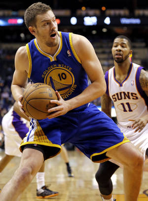 Photo - Golden State Warriors' David Lee (10) drives against Phoenix Suns' Markieff Morris (11) during the first half of an NBA basketball game on Friday, April 5, 2013, in Phoenix. (AP Photo/Matt York)