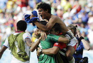 Photo - Costa Rica players celebrate with goalkeeper Keylor Navas (1) following the team's 1-0 victory over Italy during the group D World Cup soccer match between Italy and Costa Rica at the Arena Pernambuco in Recife, Brazil, Friday, June 20, 2014.  (AP Photo/Ricardo Mazalan)