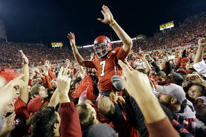 Photo - Utah quarterback Travis Wilson (7) is hoisted to the air by Utah fans after defeating Stanford 27-21 during an NCAA college football game on Saturday, Oct. 12, 2013, in Salt Lake City. (AP Photo/Rick Bowmer)