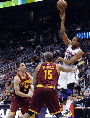 Photo - Atlanta Hawks center Al Horford (15) passes the ball under pressure from Cleveland Cavaliers' Chris Quinn (20) and Marreese Speights (15)in the first half of an NBA basketball game at Philips Arena in Atlanta, on Monday, April 1, 2013. (AP Photo/David Tulis)