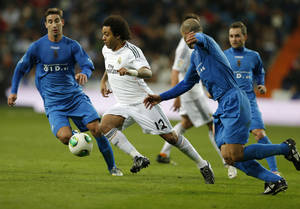 Photo - Real's Marcelo, centre takes the ball through the Xativa defence during a round-of-32, 2nd leg Copa del Rey soccer match between Real Madrid and third-division club Xativa Olimpic at the Bernabeu stadium in Madrid, Wednesday, Dec. 18, 2013. (AP Photo/Paul White)