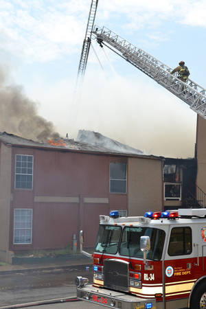 Photo - Firefighters work to tame an apartment building fire on Saturday. Photo by Zeke Campfield, The Oklahoman