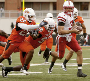 Photo - Nebraska's Taylor Martinez runs past OSU's James Thomas, left, and Darius Hart during the college football game between the Oklahoma State Cowboys (OSU) and the Nebraska Huskers (NU) at Boone Pickens Stadium in Stillwater, Okla., Saturday, Oct. 23, 2010. Photo by Bryan Terry, The Oklahoman