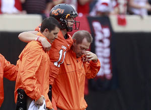 Photo -   Oklahoma State quarterback Wes Lunt, center, is helped off the field after an injury in the first quarter of an NCAA college football game against Louisiana-Lafayette in Stillwater, Okla., Saturday, Sept. 15, 2012. (AP Photo/Sue Ogrocki)