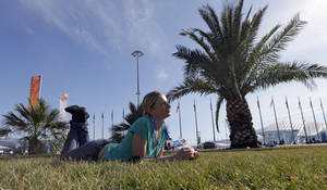 Photo - Oxsana Kharitonova lyes on the grass while posing for a photograph with friends on a sunny warm day at the 2014 Winter Olympics, Wednesday, Feb. 12, 2014, in Sochi, Russia. (AP Photo/David J. Phillip )