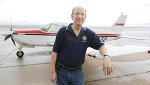 Photo - Pat Cohenour leans on a plane at Wiley Post Airport in Oklahoma City. Cohenour gives kids flights in airplanes through the Young Eagles national program. Photo By Steve Gooch, The Oklahoman
