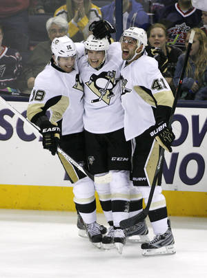 Photo - Pittsburgh Penguins' Beau Bennett (19), center, celebrates with teammates James Neal (18) and Robert Bortuzzo (41) after scoring to make it 2-0 during the third period of an NHL hockey game, Friday, March 28, 2014, in Columbus, Ohio. (AP Photo/Mike Munden)