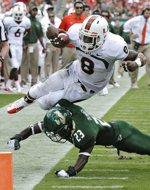 Photo - Miami running back Duke Johnson (8) is knocked out of bounds short of the goal line by South Florida defensive back Kenneth Durden (23) during the second quarter of an NCAA college football game Saturday, Sept. 28, 2013, in Tampa, Fla. (AP Photo/Chris O'Meara)
