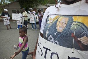 Photo -   Bree Coleman, right, wears a tee shirt with a picture imprinted on it she says she made of Chavis Carter, in Jonesboro, Ark., as Sakhiya Bell, 4, runs past Tuesday, Aug. 21, 2012. About 20 people marched in protest of the July 28 death of Carter that was ruled a suicide in the back of a Jonesboro Police Department car. (AP Photo/Danny Johnston)