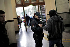 Photo - A police officer checks the identification of a passerby in the central train station, Wednesday, Jan. 29, 2014, in Sochi, Russia, home of the upcoming 2014 Winter Olympics. (AP Photo/David Goldman)