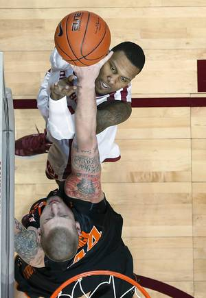 Photo - Oklahoma forward Romero Osby, top, shoots over Oklahoma State forward Philip Jurick, bottom, in the first half of an NCAA college basketball game in Norman, Okla., Saturday, Jan. 12, 2013. (AP Photo/Sue Ogrocki)
