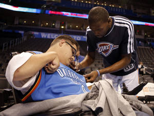 Photo - Kevin Durant signs  Andrew Rains shirt before an NBA basketball game between the Oklahoma City Thunder and the Golden State Warriors at Chesapeake Energy Arena in Oklahoma City, Sunday, Nov. 18, 2012.  Andrew Rains suffers from cerebral palsy, and is attending his first Thunder game.  He never misses a game on television.  Photo by Garett Fisbeck, The Oklahoman