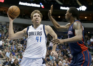 Photo - Dallas Mavericks' Dirk Nowitzki (41) of Germany drives to the basket against Detroit Pistons' Kentavious Caldwell-Pope (5) in the second half of an NBA basketball game, Sunday, Jan. 26, 2014, in Dallas. Nowitzki had a game-high 28-points in the 116-106 Mavericks win. (AP Photo/Tony Gutierrez)