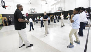 Photo - Martial arts instructor Ken Banks, at left, leads students Jan. 23 in a martial arts class taught by Police Athletic League staff members at Martin Luther King Elementary School in Oklahoma City. Photo by Paul B. Southerland, The Oklahoman