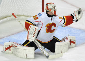 Photo - Calgary Flames goalie Reto Berra of Switzerland, makes a save during the first period of an NHL hockey game against the Chicago Blackhawks in Chicago, Sunday, Nov. 3, 2013. (AP Photo/Paul Beaty)