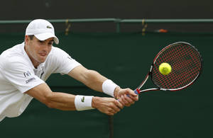Photo - John Isner of the U.S. plays a return to Feliciano Lopez of Spain during their men's singles match at the All England Lawn Tennis Championships in Wimbledon, London, Monday, June 30, 2014. (AP Photo/Sang Tan)