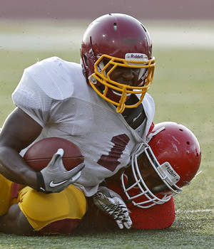 photo - Putnam City North's Tae Moore is brought down by Lawton's BJ Scott during a high school football scrimmage at Putnam City High School in Warr Acres, Okla., Thursday, August 16, 2012. Photo by Bryan Terry, The Oklahoman