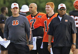 Photo -   Cincinnati Bengals head coach Marvin Lewis, right, watches practice with offensive coordinator Jay Gruden, left, and quarterbacks Bruce Gradkowski (7) and Andy Dalton during NFL football training camp on Saturday, July 28, 2012, in Cincinnati. (AP Photo/Al Behrman)