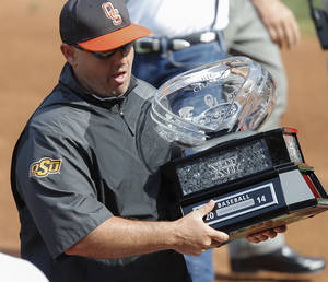Photo - Oklahoma State coach Josh Holliday carries the Big 12 regular season Championship that the Cowboys were presented before the start of the bedlam matchup between the University of Oklahoma and Oklahoma State University in the Phillips 66 Big 12 Baseball Championship in Oklahoma City, Okla. on Wednesday, May 21, 2014.   Photo by Chris Landsberger, The Oklahoman