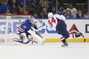 Photo - Washington Capitals center Mikhail Grabovski (84), of Germany, scores on New York Rangers goalie Henrik Lundqvist (30), of Sweden, on a penalty shot in the second period of an NHL hockey game on Sunday, Dec. 8, 2013, in New York. (AP Photo/John Minchillo)