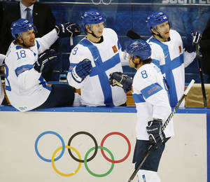 Photo - Finland forward Teemu Selanne (8) is congratulated by his teammates after scoring a goal against Norway during the 2014 Winter Olympics men's ice hockey game at Shayba Arena, Friday, Feb. 14, 2014, in Sochi, Russia. (AP Photo/Petr David Josek)