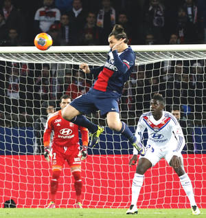 Photo - Paris Saint Germain's Zlatan Ibrahimovic of Sweden, center, heads the ball as Lyon's goalkeeper Remy Vercoutre, left, and Samuel Um Titti look on during their French League One soccer match, Sunday Dec. 1, 2013, in Parc des Princes stadium, in Paris, France. (AP Photo/Jacques Brinon)