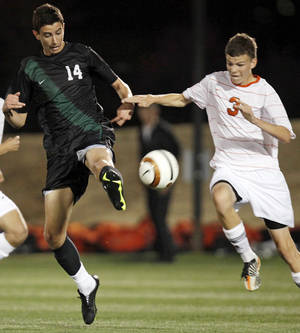 photo - Norman North's Mauro Cichero (14) kicks the ball next to Norman's Zach Terry (3) during a boys high school soccer game between Norman and Norman North at the OU Soccer Complex in Norman, Okla., Thursday, March 15, 2012. Photo by Nate Billings, The Oklahoman
