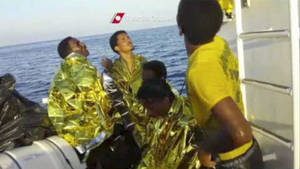 Photo - In this image made from video provided by the Italian Coast Guard and recorded on Thursday, Oct. 3, 2013, survivors of a ship transporting hundreds of migrants which caught fire and sank wear thermal rescue blankets after being rescued by the Italian Coast Guard off the Sicilian island of Lampedusa, Italy. Authorities on Friday, Oct. 4 are contending with choppy waters in the search for dozens of migrants believed to have drowned after their rickety boat caught fire and sank off the coast of the southern Italian island of Lampedusa. (AP Photo/Italian Coast Guard)