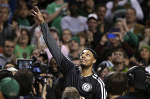 Photo - Brooklyn Nets forward Paul Pierce, center, formerly of the Boston Celtics, waves to the crowd during a tribute to him in an NBA basketball game against the Boston Celtics, Sunday, Jan. 26, 2014, in Boston. (AP Photo/Steven Senne)