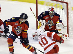 Photo - Detroit Red Wings left wing Henrik Zetterberg (40) scores against Florida Panthers goalie Scott Clemmensen (30) as Panthers' Dmitry Kulikov (7) defends during the first period of an NHL hockey game in Sunrise, Fla., Saturday, Dec. 28, 2013. (AP Photo/Alan Diaz)