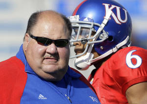 photo - FILE - In this Sept. 26, 2009, file photo, Kansas coach Mark Mangino stands with his team before the start of an NCAA college football game against Southern Miss in Lawrence, Kan. Mangino has resigned two years after leading the Jayhawks to the greatest season in their checkered football history. (AP Photo/Orlin Wagner, File) ORG XMIT: NY184