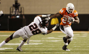 Photo - Cowboy Kendall Hunter (24) knocks away LeBron Moore (28) during the college football game between Oklahoma State University (OSU) and Texas Tech University (TT) at Boone Pickens Stadium in Stillwater, Okla. Photo by Doug Hoke, The Oklahoman