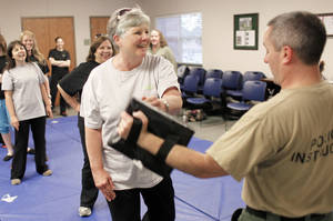 Photo - Edmond city employee Linda Cresse practices punches with police Sgt. Jeff Richardson during a four-week self-defense class. PHOTOs BY DOUG HOKE, THE OKLAHOMAN