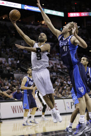 Photo - San Antonio Spurs' Tony Parker (9), of France, shoots around Dallas Mavericks' Dirk Nowitzki (41), of Germany, during the first half of Game 5 of the opening-round NBA basketball playoff series on Wednesday, April 30, 2014, in San Antonio. (AP Photo/Eric Gay)