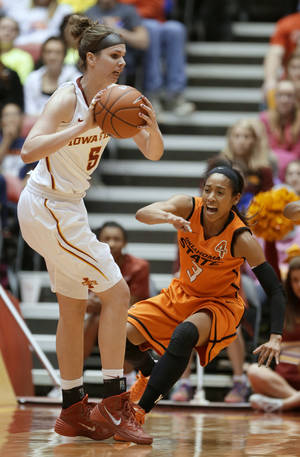 Photo - Iowa State forward Hallie Christofferson, left, passes in front of Oklahoma State guard Tiffany Bias during the first half of an NCAA college basketball game, Saturday, Jan. 11, 2014, in Ames, Iowa. (AP Photo/Charlie Neibergall)