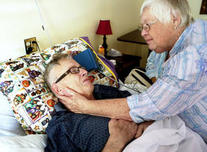 Photo - Bob Matthews is comforted by his wife, B.J., on Friday as he continues to recover from the effects of West Nile virus. Photo by Bryan Terry, The Oklahoman