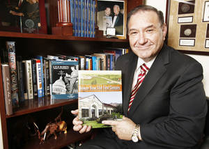 "Photo - Attorney Bob Burke shows his book ""Broken Bow: The First Century."" The book about his hometown is the 100th book Burke has authored. Photo BY PAUL B. SOUTHERLAND, THE OKLAHOMAN"