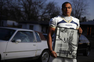 Photo - Quintaz Struble holds a photo of his father Mandrell Dean in front of his 1986 Cutlass Supreme in Oklahoma City home on Thursday, Jan. 12, 2012. Photo by Bryan Terry, The Oklahoman