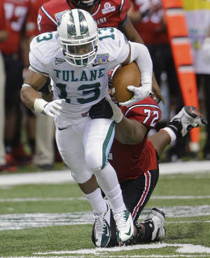 Photo - Tulane cornerback Derrick Strozier (13) is stopped by Louisiana-Lafayette offensive linesman Terry Johnson (72) during the second half of the New Orleans Bowl NCAA college football game in New Orleans, Saturday, Dec. 21, 2013.  (AP Photo/Bill Haber)