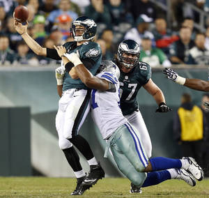 Photo -   Philadelphia Eagles quarterback Nick Foles, left, is hit by Dallas Cowboys' Jason Hatcher as he throws in the second half of an NFL football game, Sunday, Nov. 11, 2012, in Philadelphia. (AP Photo/Julio Cortez)